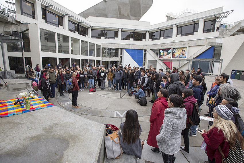 A crowd gathers for a memorial in front of the Cesar Chavez Student Center.
