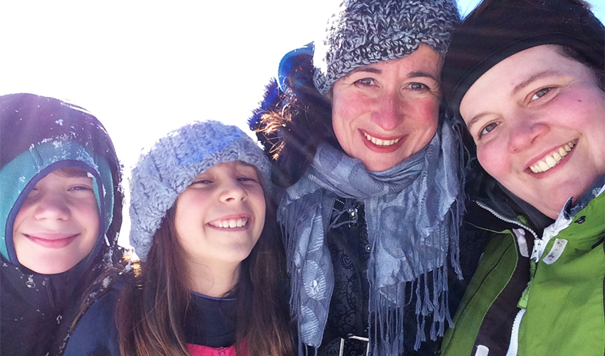 Assistant Professor Ana Luengo's son Niklas, daughter Milena, Ana Luengo and partner Lani Phillips, all smiling and bundled up in winter clothing.