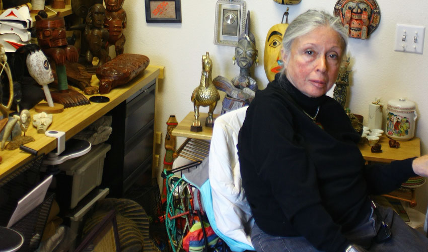SF State Professor and Chair of Philosophy Anita Silvers in her office, surrounded by colorful mementoes and artwork —gifts given by students and colleagues during the past 50 years.