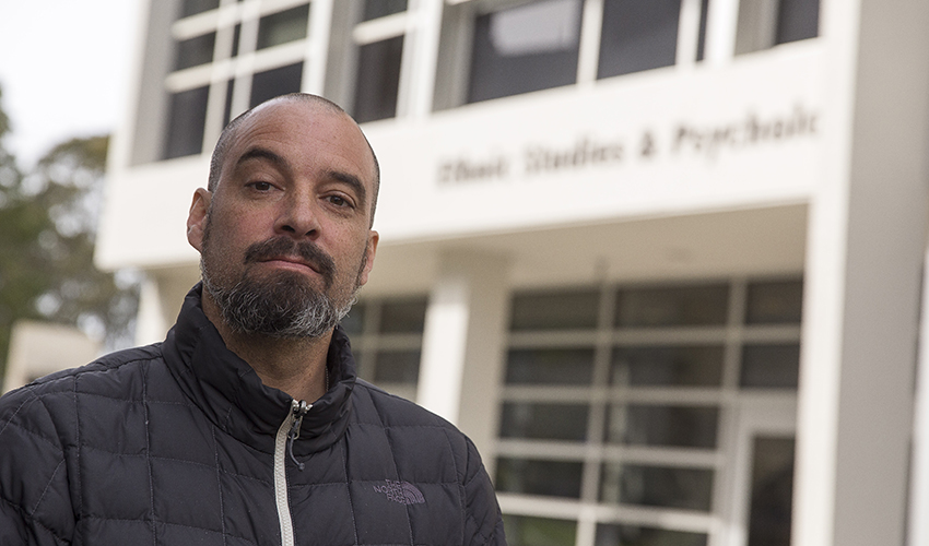 SF State Associate Professor Jeff Duncan-Andrade stands in front of the ethnic studies building.