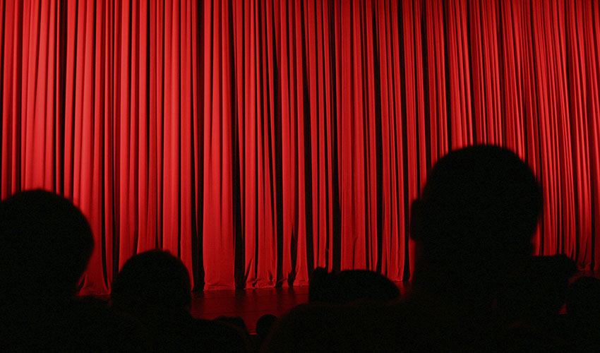 Photo of a theater stage with a red curtain and silhouettes of people facing the stage