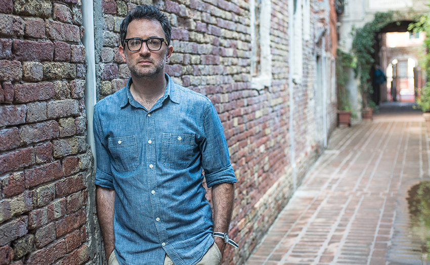 Chinan Tigay, wearing a denim work shirt with the sleeves rolled up, is standing in a cobblestone alley, leaning against a brick wall in this photo. Photo credit: Emanuele Dello Strologo