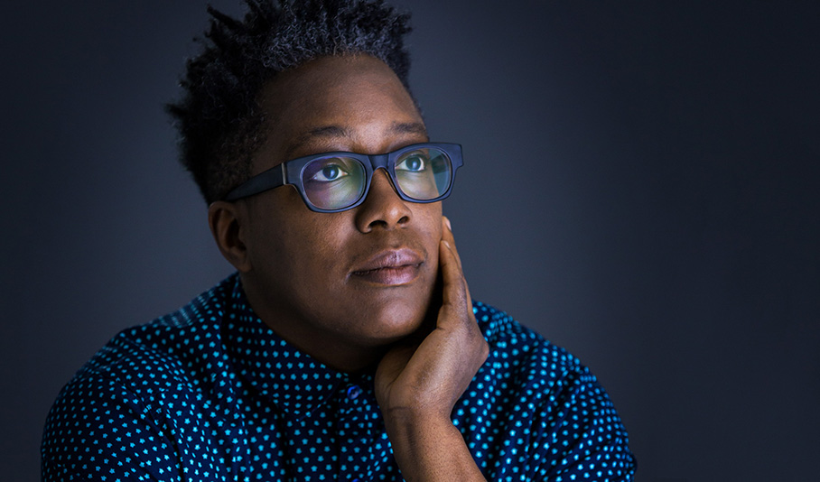 Cheryl Dunye wears a navy blue shirt with a small turquoise star pattern and purple horn-rim-style eyeglasses