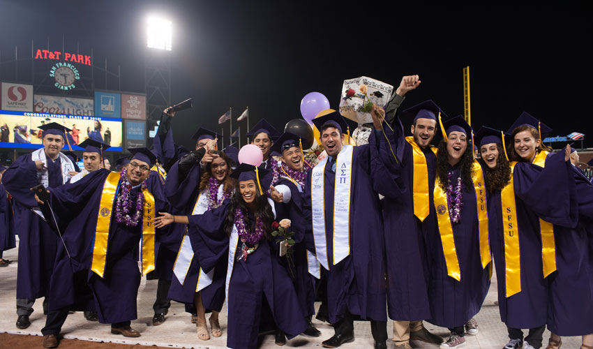 A group of purple-clad SF State graduates on the field at AT&T Park during Commencement 2016.