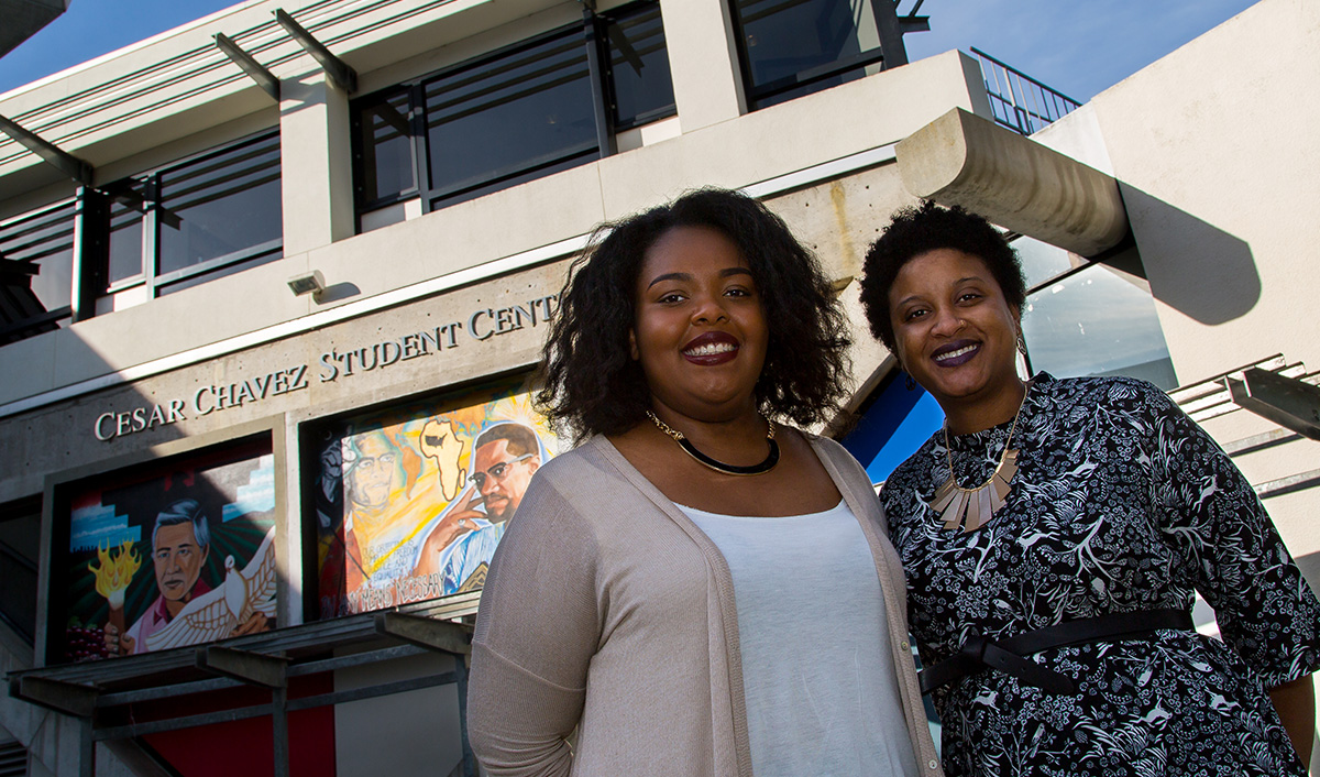 Debate champions Aliyah Shaheed and Genelle Murray are photographed in front of the Malcolm X mural on the Cesar Chavez Student Center