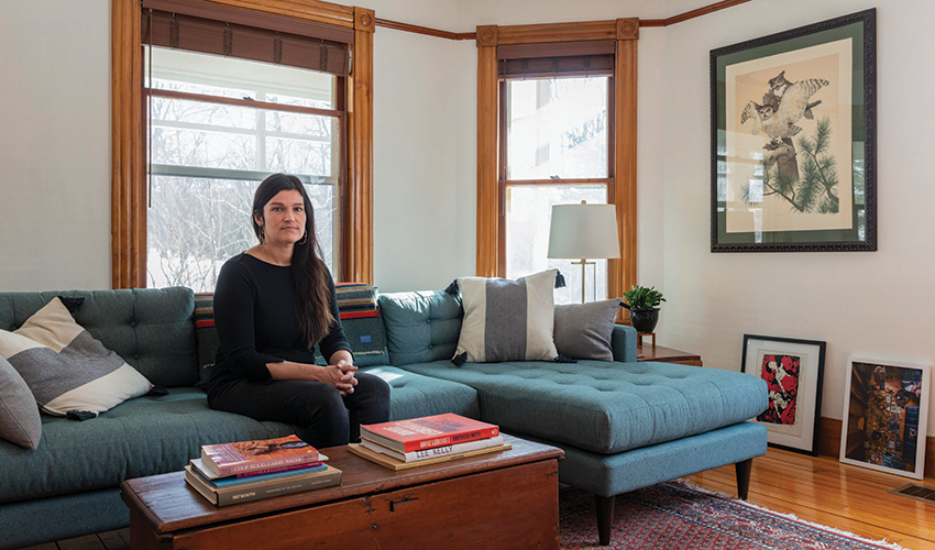 Photographer Brittany M. Powell sits on a couch inside her home