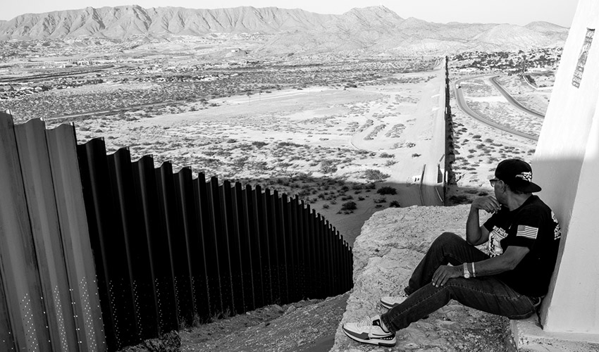 Deported U.S. Army veteran Jose Francisco Lopez Moreno overlooks the fence separating him from the United States.