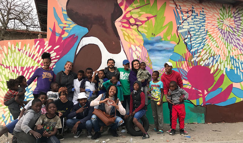 SF State early childhood education students and community members pose in front of the new community mural they painted this summer.