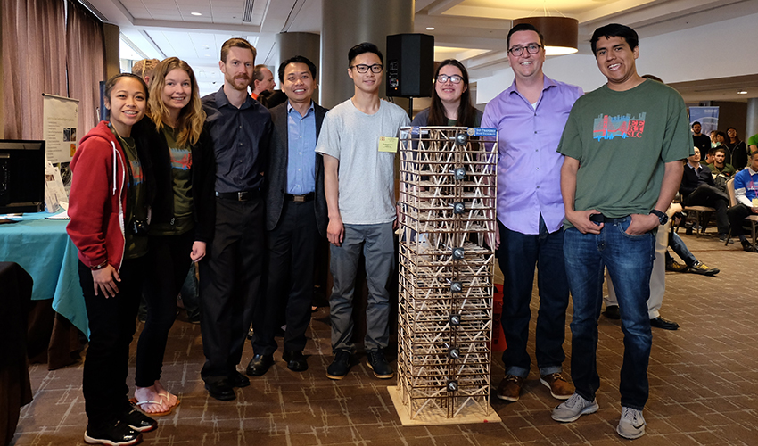 A photo of Kathleen Ocampo, Jamie Brownell, Ryan Schofield, faculty advisor Zhaoshuo Jiang, Lungyuen Lau, Marisa Araujo, project manager Stephen Pereira Schork and Omar Plata with their wood skyscraper model.