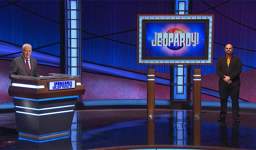 "Assistant Professor James Gilligan on the ""Jeopardy!"" set with late host Alex Trebek."