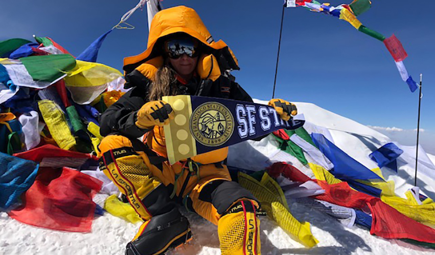 Woman wearing mountain climbing gear holds up an SF State flag at the top of a mountain.