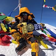 Woman wearing mountain climbing gear holds up an SF State flag at the top of a mountain