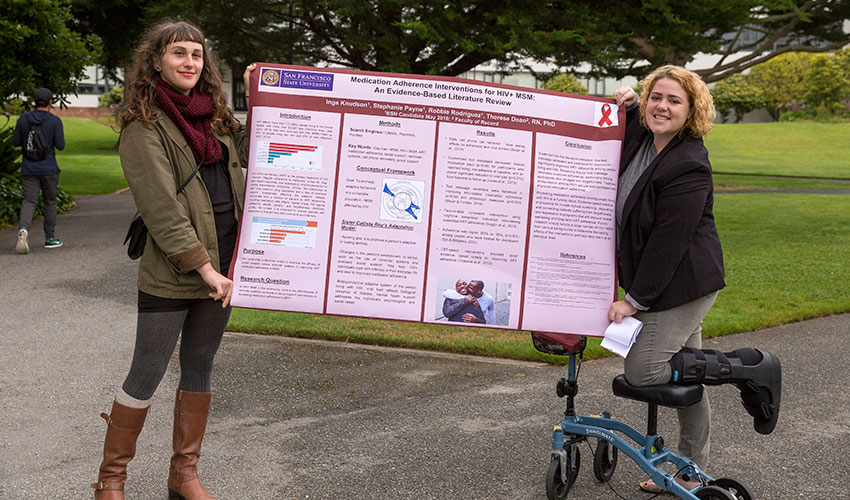 Two SF State students hold a poster that details their analysis of anti-retroviral therapy adherence among men who have HIV.
