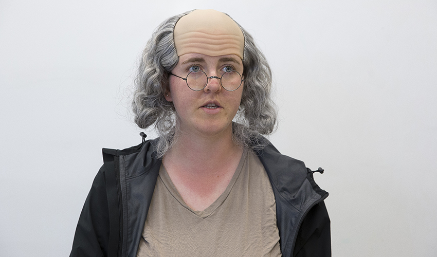 Female student dressed in a white wig and gold-plated glasses resembling Benjamin Franklin.