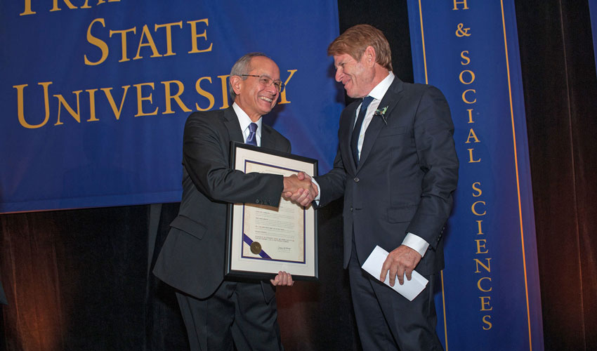 President Les Wong shaking hands with alum Gregory Fischbach as he presents Fischbach with a citation.