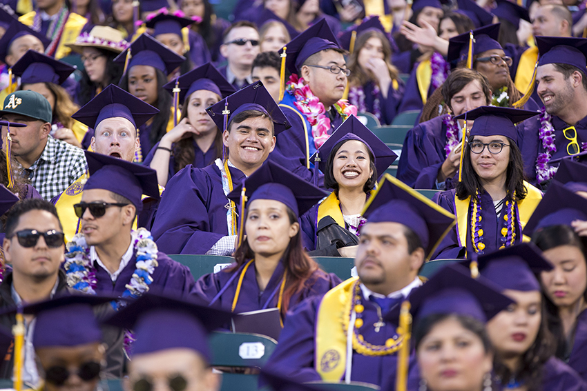 Smiling SF State graduates in their purple robes and mortarboards are in the stands at AT&T Park