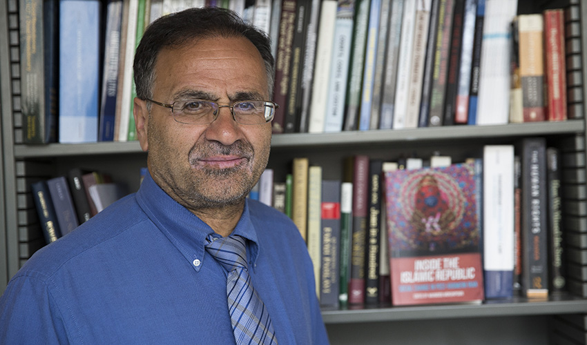 Professor stands in front of book shelf next to his book
