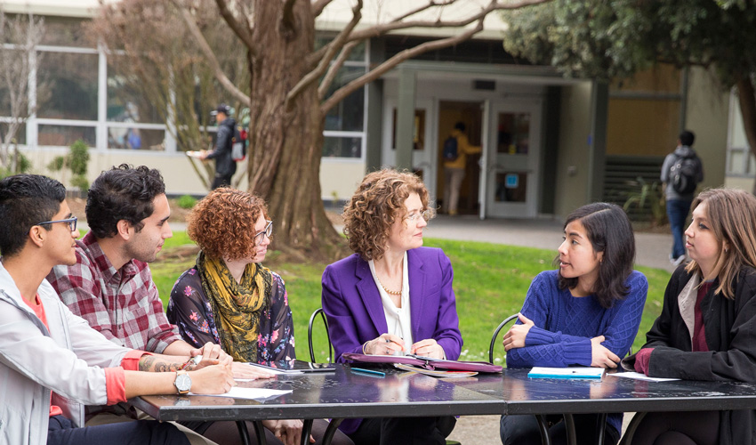 Jennifer Summit, dean of the Division of Undergraduate Education and Academic Planning, is seated at a rectangular table outdoors, flanked by five students.