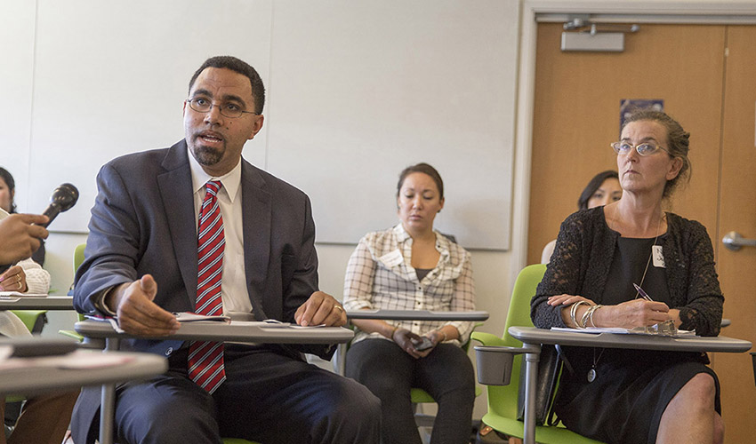 A photo of Deputy Secretary of Education John King and Undocumented Student Advisor Nancy Jodaitis during a roundtable discussion.