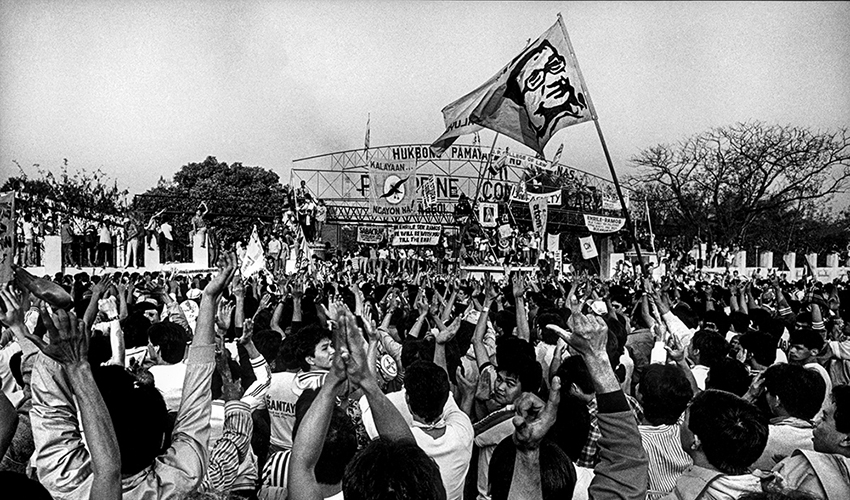 """Thousands of men and women, arms raised in the air, form the letter """"L"""" with their thumbs and forefingers to represent the word """"Laban,"""" which means """"to fight"""" In Tagalog. A flag bearing the likeness of assassinated Filipino political leader Benigno Aquino, Jr. waves over the crowd. Photo credit: Kim Komenich for the San Francisco Examiner ©2011/ The Pictorial Collection, Bancroft Library, University of California, Berkeley."""