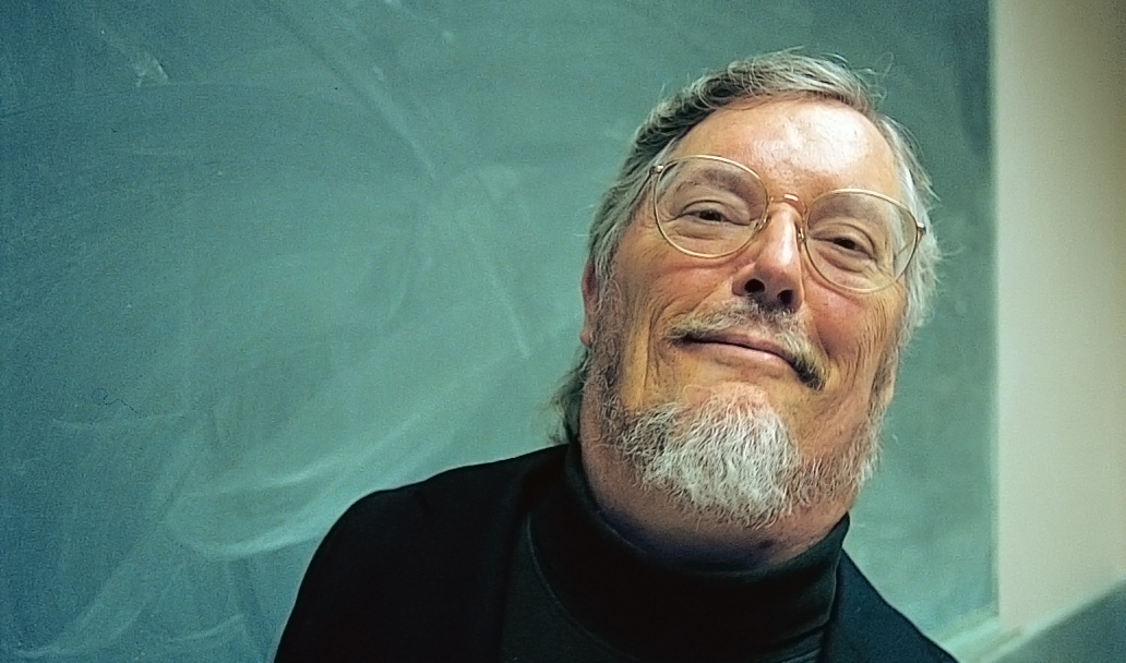 A smiling, bespectacled Paul K. Longmore in front of a green chalkboard