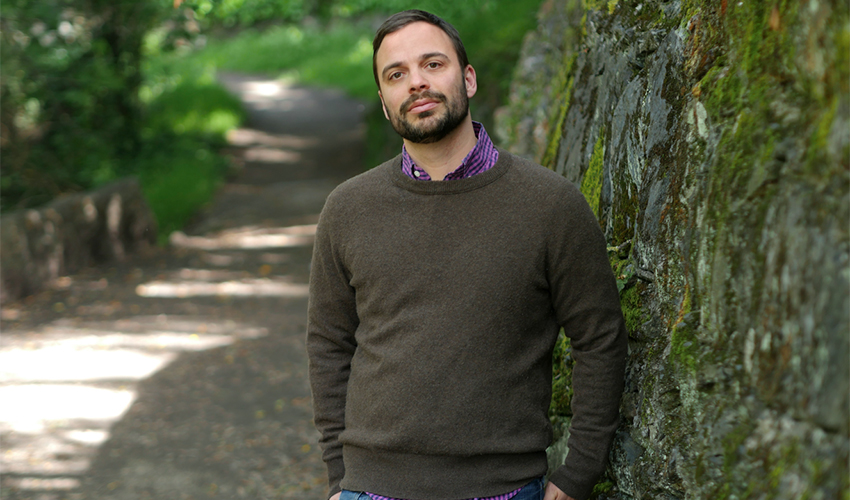 Assistant Professor of Creative Writing Michael David Lukas standing by a tree.