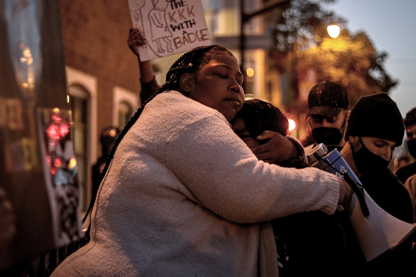 Talika Fletcher consoles a fellow protester during a vigil and march held in honor of Roger Allen and Daunte Wright.