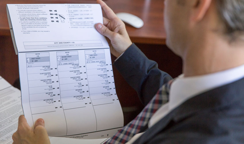 Jason McDaniel, SF State assistant professor of political science, reviews a ranked-choice voting ballot.