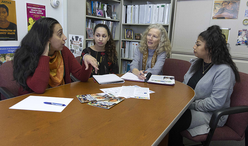 Rama Ali Kased, Director of Metro Student  Services, Sofia Kakaizada, SF State Senior and Metro student, Mary Beth Love, and Alexandra Urbina, Metro Outreach and Recruitment Coordinator, sit at a table, discussing Metro programs.
