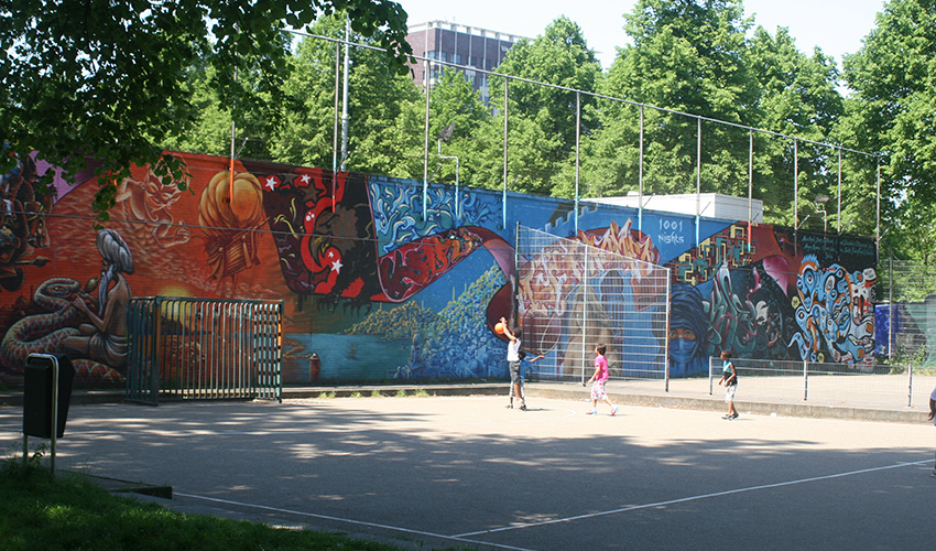 Children play basketball on an urban courtyard surrounded by colorful graffiti and plenty of trees.