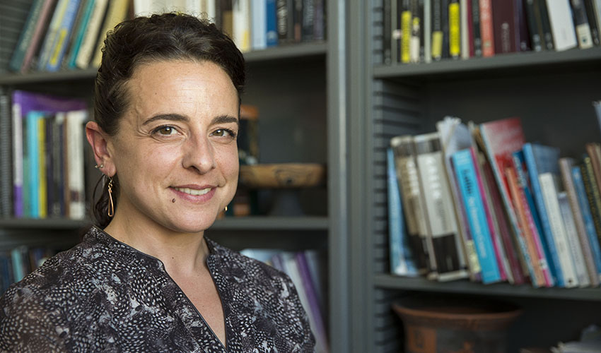 Assistant Professor Alexandra Pappas is seated in her office; the bookcase in the background is lined with books about Greek art and literature and also features a kylix, a Greek vessel used for drinking wine.