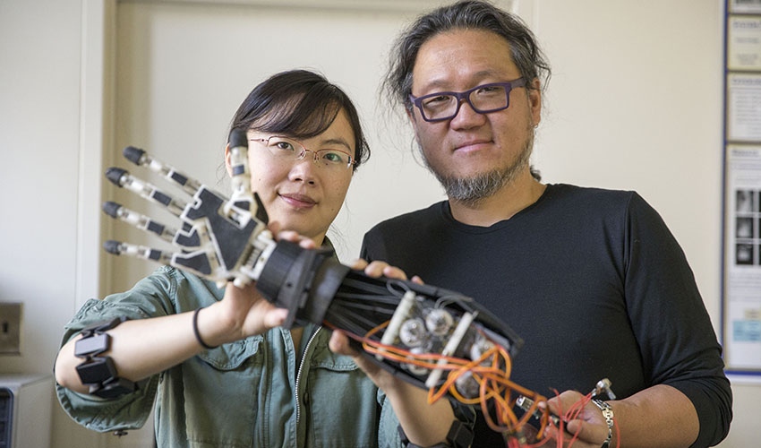 Associate Professor of Computer Science Kazunori Okada and Assistant Professor of Engineering Xiaorong Zhang in a lab with a prosthetic arm.