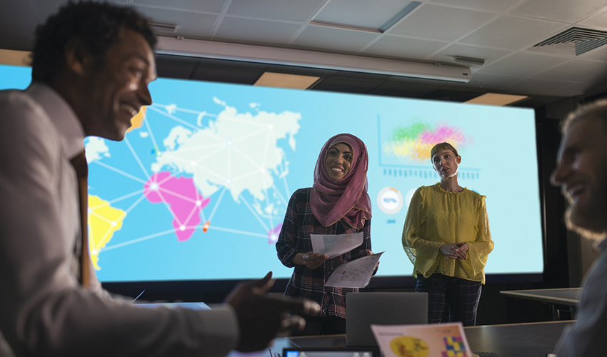 Two women listening to a man speak in front of a screen projecting a map of the world.