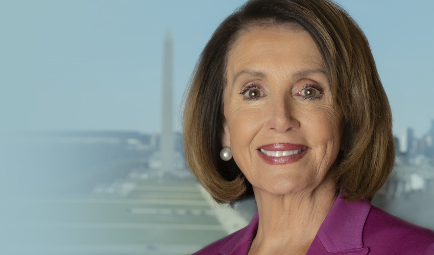 Congresswoman and Speaker of the House is pictured wearing a dark pink suit jacket and white shell; the Washington Monument can be seen in the background.