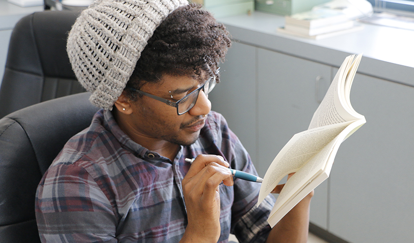 A male student holds a pencil pointed at a book he reads in a classroom.