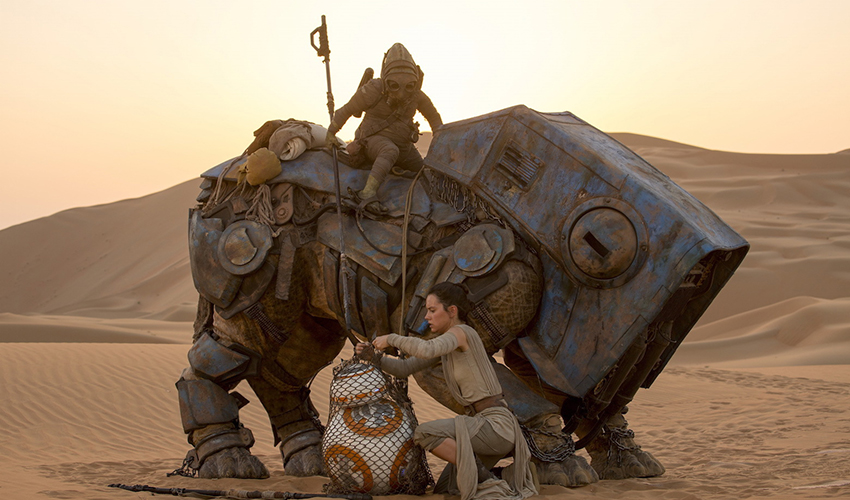 "A desert scene from ""Star Wars: The Force Awakens,"" in which the heroine Rey readies BB-8, a round android, for transport with the scavenger Teedo and his semi-mechanical Luggabeast. Photo credit: StarWars.com"