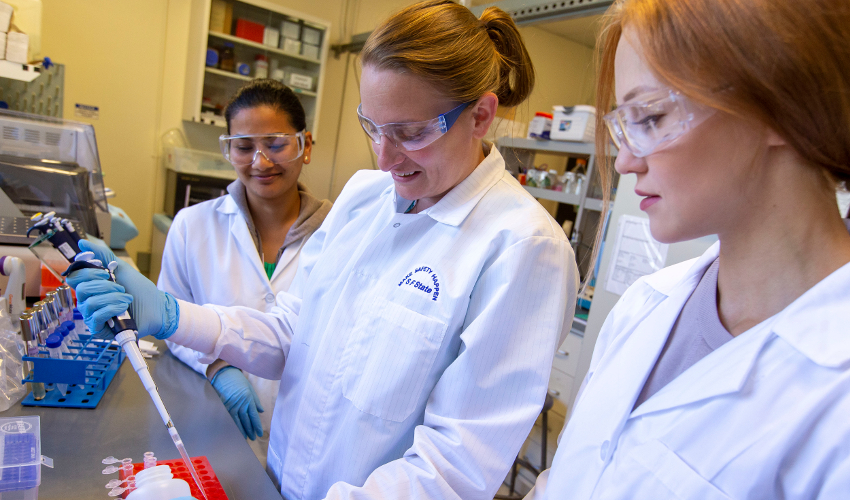Researcher in white lab coat using a pipette while two students watch