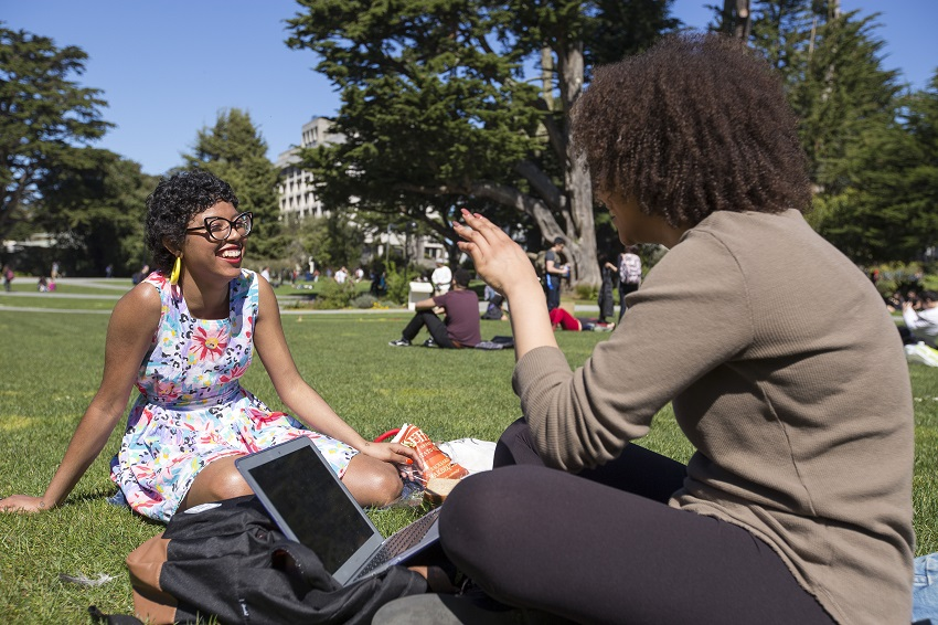 Smiling students on campus lawn