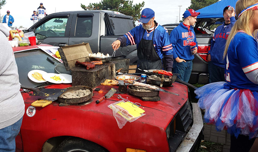 A group of Buffalo Bills fans cooks on the surface of an old Ford Pinto.