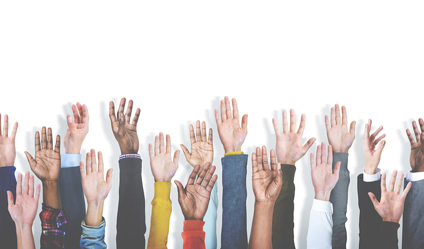 Hands raised at attention from different racial backgrounds and skin tones.