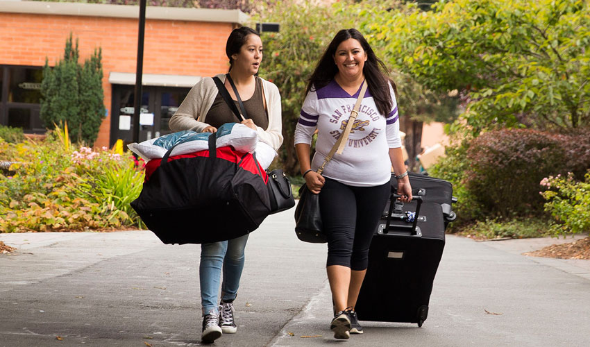 Two new SF State students carry luggage across campus toward the residence halls.