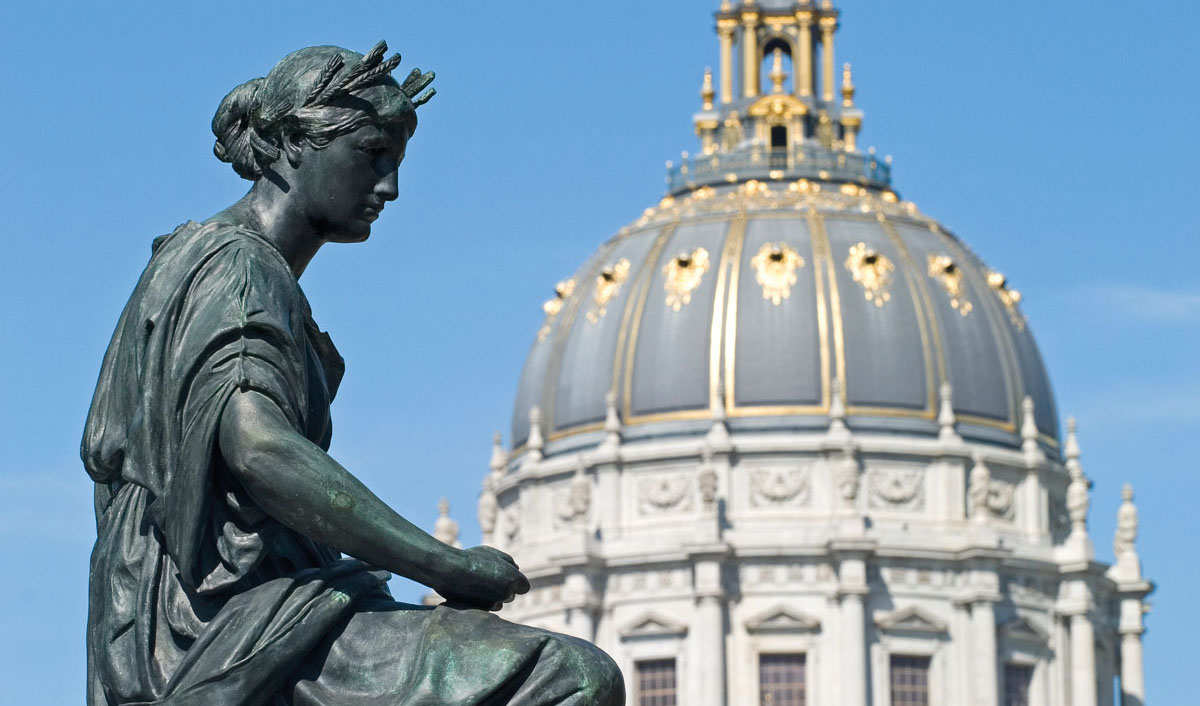 A photo of a statue and the dome of San Francisco City Hall