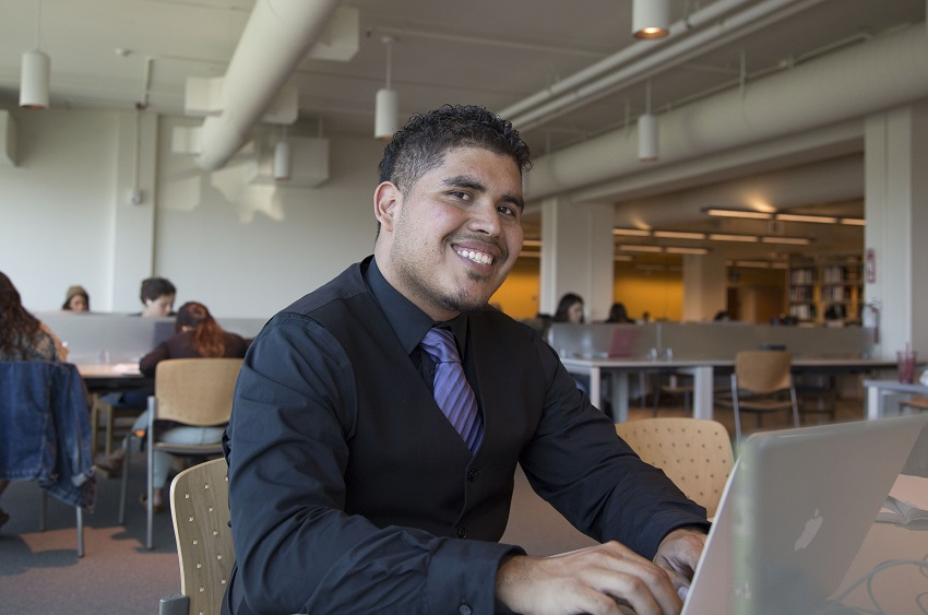 An SF State student smiles as he works on his laptop