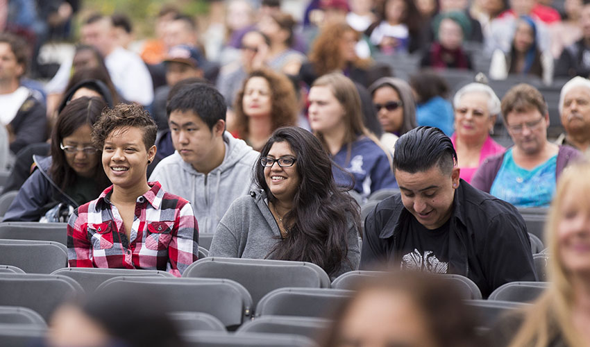 Three SF State students sitting among the audience on the quad during the Welcome Days event in August.