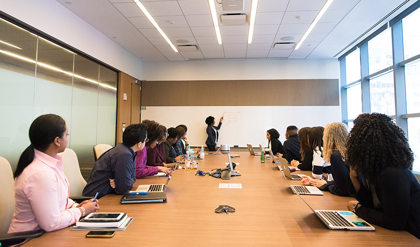 Woman speaking in a boardroom to a group of people