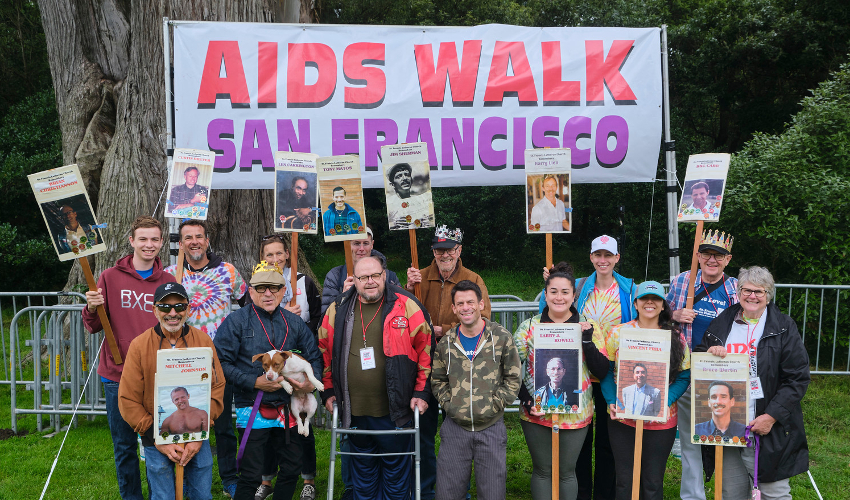 "Fourteen people holding signs in front of a banner reading ""AIDS WALK San Francisco"""