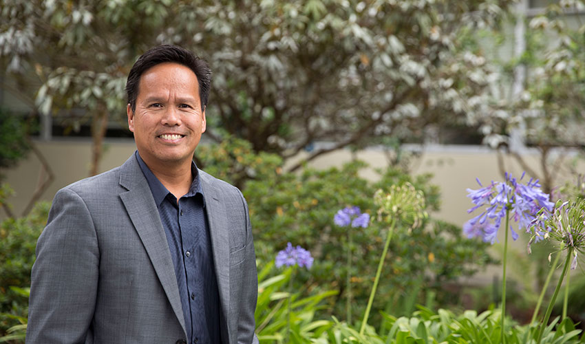 Health & Social Sciences Dean Alvin Alvarez, wearing a gray suit, stands in front of plants, trees and flowers.