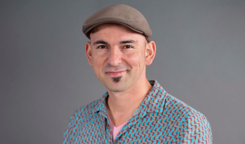 Federico Ardila, wearing a cap and a geometric-patterned shirt with, smiles at the camera