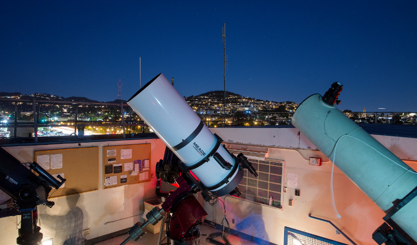 A time-lapse photo of students using three telescopes on the roof of the SF State Observatory