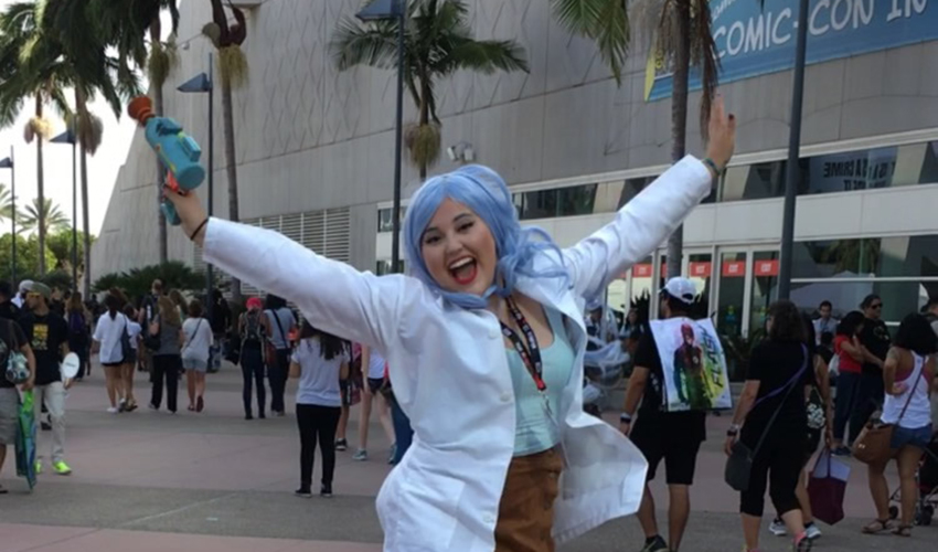 zul Sanchez-Macias wears a wig and lab coat and poses with her arms outstretched.